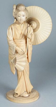 """Description: JAPANESE CARVED IVORY FIGURE, GEISHA 19th c., standing geisha, holding a parasol and fan, bottom signed with kanji and incised cherry branch, 10""""h Umbrella handle warped."""