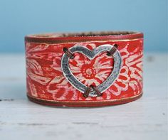 A little love. Painted embossed belt leather with fine silver open heart.  By Ann Goodall