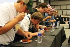Contestants in the bacon eating contest work to eat their way through a quarter pound of bacon. Photo by Sarina Rhinehart/Ames Tribune  http://amestrib.com/news/bacon-lovers-leave-expo-satisfied