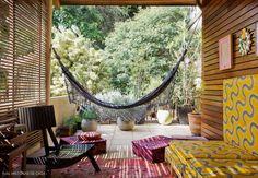 Essa varanda colorida tem rede de balanço e futons com estampas variadas.