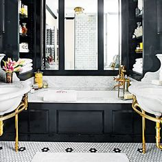 Small amounts of bronze pops against the black cabinets and white stone of this bathroom