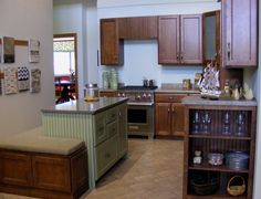 Walnut cabinets with a painted island incorporating beadboard and with bench seating.
