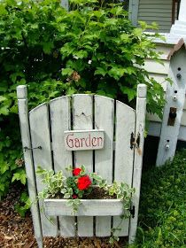 Outdoor Areas: Garden Gate Planter W,Red Geranium & leafy vine foliage
