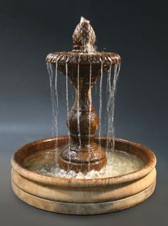 Tall Fountain with a long waterfall creates splash outside of bowl...  self waters plants on the perimeter