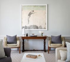 13 tips for making a large open space feel cozier. Love this idea of two occasional chairs with a console table and artwork.