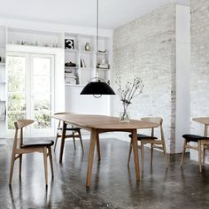 White rough walls, dark mottled polished concrete floor. Warm wood furniture. Nice combo!