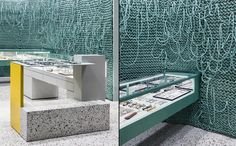A feature wall made of seeming knitted thick teal wiring climbs the back wall and becomes a focus within the store. The collection of glasses are displayed throughout in the backlit shelves, tables or encased in the glass counters.