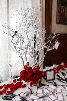 Sprayed white branches holding crystal beads and red roses as the base forms a very winter wonderland table   HappyWedd.com