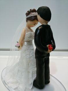 Topo de bolo - Noivos (noivo beijando testa da noiva, segurando caixa com alianças e noiva segurando buquê). Vestido de renda na noiva