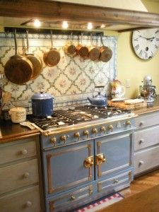Classic La Cornue range in French Blue looks perfect with painted French tiles and copper pots and pans for a French Country Kitchen