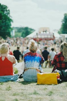3 Woman Sitting on Green Grass Field Facing the Gathering People during Daytime