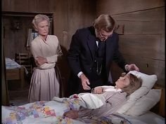 Doc Baker visits a sick boy in Season 2, Episode 15 who is cozy beneath a patchwork quilt made of which appears to be an Irish Chain quilt. The quilt is made mostly of 3x3 inch square scraps which are stitched together to form an X-like pattern on a white background.