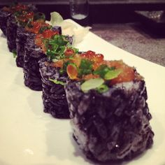 The Beauty: squid ink sushi rice, scallop tempura & fresh crab mixed with Japanese mayo, shiso leaf & lettuce, topped with ikura, green onions & garlic radish