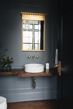 A French brass mirror hangs from a gray wall fitted with gray trim moldings over. - A French brass mirror hangs from a gray wall fitted with gray trim moldings over a wall mount vintage brass cross handle faucet. Powder Room Sink, Vintage Bathroom, Bathroom Makeover, Grey Walls, Small Toilet, Small Bathroom, Modern Bathroom, Bathroom Design, Bathroom Decor