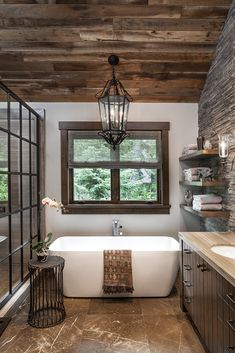 Inside a Stylish Mountain Home on Lake Tahoe Designed by Jeff Andrews - A vintage light from Paris hangs above the tub in the master bathroom, which is accented by a side - Rustic Bathrooms, Rustic Cabin Bathroom, Lodge Bathroom, Lake House Bathroom, Rustic Bathroom Fixtures, Log Cabin Bathrooms, Rustic Bathroom Lighting, Rustic Bathroom Designs, Beautiful Bathrooms