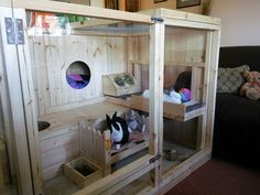 Wooden indoor rabbit cage with a see through glass front. This would be a good setup for chinchillas with a few more hideouts and ledges.