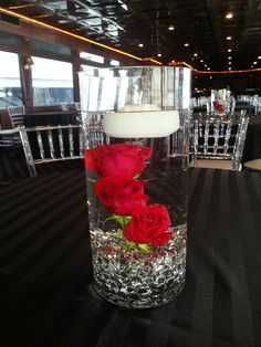 3 red roses submerged with floating candle for a Centerpiece