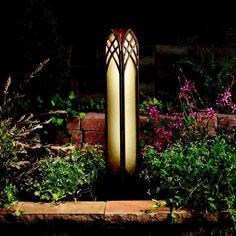 borne de jardin en acier Corten et verre opaque, plantes vertes et fleurs roses