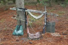 Here the Tree Lounge tree stand is mounted on a tree ready to climb. The bags of gear and guns are daisy-chained up to be hoisted to the stand one by one.