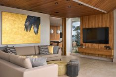 This modern living room has a wood accent wall and pillows that reflect the colors in the large artwork on the wall. #LivingRoom