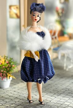 Gay Parisienne™ Barbie® Doll   Barbie Collector  chic in her classic dark blue bubble dress with tiny white polka-dots. Around her shoulders is a fabulous faux fur stole, and sitting atop her head is a sophisticated veiled headband hat