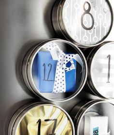 A close-up of a magnetic stainless steel container attached to a fridge and filled with a little wrapped present.