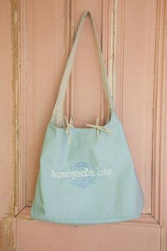 Fabric: sturdy cotton canvas  Color: 'something blue' w/ 'honeymoon tan' inside  Style Keywords: honeymoon bag, travel tote, beach wedding bag  Measurements: approx 11x18x9  Size: OS. Yours for FREE when you book a party of 7 or more with Maritza for hair