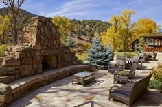 Outside, a sandstone patio with a rock fireplace overlooks a creek.-SR