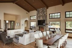 Living Room: Rustic Living Room And Dining Room With Open Plan. rustic living room. large living room. living and dining room. white sofa. tall ceiling. wooden table. natural window shade.