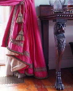 Detail of a fuschia silk curtain with tassels and brocade trimmings beside a Georgian sidetable with carved legs