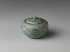 Small jar and cover with decoration of chrysanthemums, cranes, and clouds Period: Goryeo dynasty (918–1392) Date: late 13th century Culture: Korea Medium: Stoneware with gold and inlaid design under celadon glaze