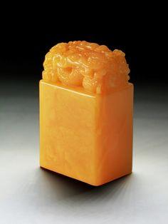 雞油黃蜜蠟雕龍鈕大印章 An Unusual Chinese Carved Baltic Amber MILA Seal: extremely rare, of rectangular section, finely carved from the whole piece of Baltic Amber Mila as a seal with an encircling dragon on top, the material of rich bright yellow tone with natural inclusions, weighing 84. 34 grams Size: H: 68mm; W: 42mm; D: 31mm; Weight: 84. 34 grams Estimate: $10,000.00 to $20,000.00
