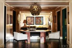 The custom-made parchment-and-brass dining table is flanked by Vladimir Kagan armchairs covered in Groundworks linen by Kelly Wearstler, and the circa-1960s chandelier is Spanish; paintings by Fabrice Penaux hang on a wall of mirror tiles.   - ELLEDecor.com