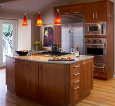 Bright red pendant lights offer a vivid contrast to this largely neutral kitchen