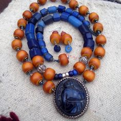 The Curious Bead Designs |  A double  sided pendant from Nepal is combined with African 'Amber' beads from Egypt and old blue Padre, and multi facetted 'Russian blues' which are 100 - 200 years old.