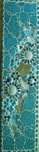Mixed media mosaic, materials include glass nuggets, beads, buttons, washers, glass shapes, mirror pieces.