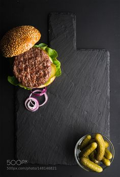 Pic: Fresh homemade burger on dark slate stone board pickles and sliced onion over black background.