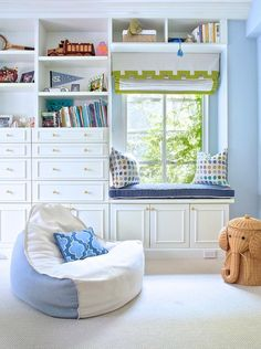A two tone blue and white bean bag chair topped with a blue trellis pillow sits on beige carpeted floors in front of white built-in book shelves positioned above dresser boasting cabinet doors fitted with brass pulls.