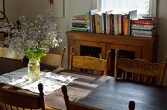 Wood table & chairs, fresh flowers, books, light.