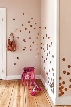Gold foil circles taped to the wall in a bland room.