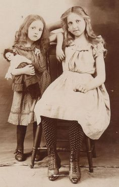 Vintage cabinet card photograph two young girls with doll,  ( victorian era 1837-1901 )