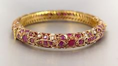 9K RUBY AND SEED PEARL BANGLE BRACELET: 9K yellow gold bangle bracelet contains 88 round mixed cut rubies, approx. 8.00 Ctw. Accented with 54 seed pearls (2 pearls are missing). The rubies and pearls are prong set. Filigree hinged bangle with locking closure and figure eight safety clasp. Weight: 37.9 grams. Approx. 2 1/4'' diameter.