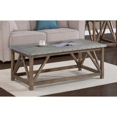 Add a stylish accent to your living room with this zinc-top wood coffee table. The nailhead details on the top of the table give it a unique look, and the wood-and-zinc construction makes this coffee table sturdy enough for years of use.