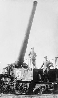 """German soldiers in captured French railway guns. One of the soldiers points to the inscription on Board the """"Contre la Grosse Bertha""""."""