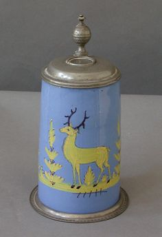German faience tankard, ca. 1750, with muffle decoration (overpainting fired at a low temperature)showing a stag in a wooded landscape. Pewter base and hinged lid. Minor imperfuctions.  H:10, Diameter:5½, excluding handle.  Ref. #72-31D