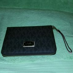 """Like new MK mini ipad holder Protect your tablet while showing off your classy sense of style with this signature printed MICHAEL Michael Kors tablet mini case.Featured in brownTablet mini caseZip around closureSignature printTablet mini compatibleDimensions: 5.75"""" x 8"""" x 1""""PVCImported Michael Kors Accessories Tablet Cases"""