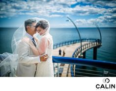 Photography by Calin - BRIDE AND GROOM HUGGING AT BRANT STREET PIER:   As a Toronto wedding photographer, I shoot weddings all over the GTA including locations in Burlington and Hamilton. For this wedding, the couple decided to have the first look on Brant Street Pier, which is a beautiful location for engagement and wedding portraits. Immediately after the unveiling, we took a few creative shots and some formal photos.