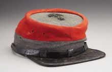 "South Carolina Artillery Officer's Kepi. 1 3/8"" gray wool band at the base, the crown of high quality red wool with the top of the crown made of the same gray wool as the base. Separately affixed, with stitches so small that they are barely detectable, is a 2"" silver bullion palmetto tree designating South Carolina. The visor of the has is covered with black oil cloth on the top and green oil cloth on the bottom, stitched binding also of black oil cloth."