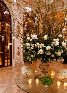 Candles hanging on the beautiful floral arrangement with branches, white roses and leaves.