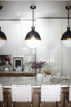 Wonderful mix of glossy white cabinets and dramatic light fixtures.  Mixing the drama of black, white, gold, and silver with a personal touch makes for a comfortable sophiticated modern space.